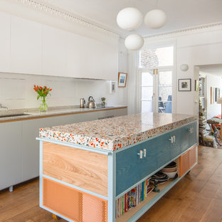 Bild på ett funkis grå grått kök och matrum, med bänkskiva i terrazo, mellanmörkt trägolv, en köksö och brunt golv