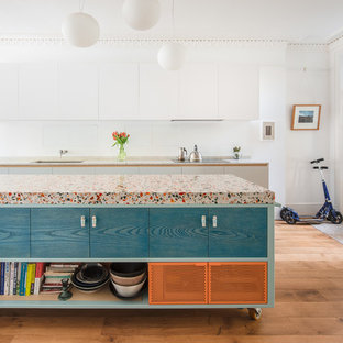 Foto på ett stort funkis flerfärgad linjärt kök och matrum, med bänkskiva i terrazo, mellanmörkt trägolv, en köksö, brunt golv, släta luckor, en undermonterad diskho och blå skåp