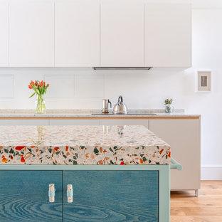 Moderne Wohnküche mit Arbeitsplatte aus Terrazzo, braunem Holzboden, Kücheninsel, braunem Boden und bunter Arbeitsplatte in London