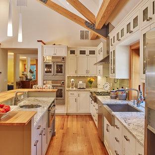 Offene Klassische Küche in L-Form mit Glasfronten, weißen Schränken, Granit-Arbeitsplatte, Küchenrückwand in Grün, Rückwand aus Glasfliesen, Küchengeräten aus Edelstahl, hellem Holzboden und Kücheninsel in Boston
