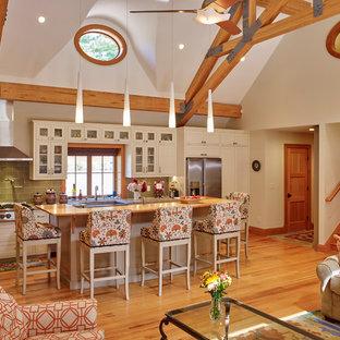 Klassisk inredning av ett kök, med luckor med glaspanel, vita skåp, granitbänkskiva, grönt stänkskydd, stänkskydd i glaskakel, rostfria vitvaror, ljust trägolv och en köksö