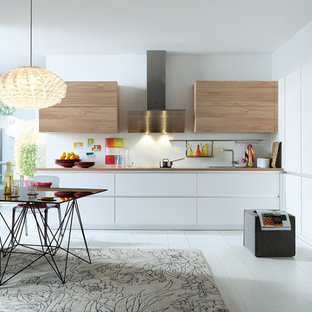 Design ideas for a medium sized modern l-shaped kitchen/diner in Surrey with flat-panel cabinets, white cabinets, laminate countertops, stainless steel appliances, painted wood flooring and no island.
