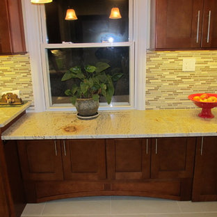 Small traditional l-shaped kitchen pantry in New York with shaker cabinets, light wood cabinets, granite benchtops, beige splashback, glass tile splashback, stainless steel appliances, porcelain floors and no island.
