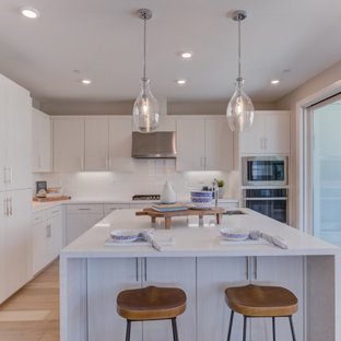 Open concept kitchen pictures - Inspiration for a l-shaped open concept kitchen remodel in San Francisco with flat-panel cabinets, white cabinets, an island and white countertops