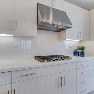 Open concept kitchen designs - L-shaped open concept kitchen photo in San Francisco with flat-panel cabinets, white cabinets, stainless steel appliances, an island and white countertops