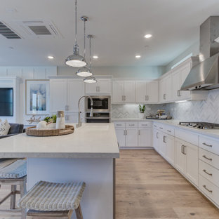 Open concept kitchen pictures - Example of a l-shaped open concept kitchen design in San Francisco with an undermount sink, recessed-panel cabinets, white cabinets, stainless steel appliances and an island