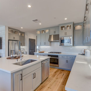 Open concept kitchen remodeling - Inspiration for a l-shaped open concept kitchen remodel in San Francisco with an undermount sink, recessed-panel cabinets, gray cabinets, stainless steel appliances and an island