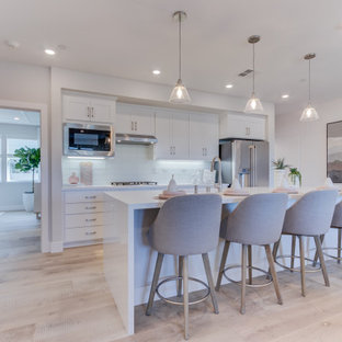 Open concept kitchen designs - Example of a single-wall open concept kitchen design in San Francisco with an undermount sink, recessed-panel cabinets, stainless steel appliances and an island