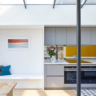 Contemporary kitchen/diner in London with flat-panel cabinets, grey cabinets, mirror splashback, an island, multi-coloured floors and white worktops.