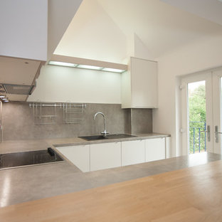 This is an example of a mid-sized contemporary u-shaped eat-in kitchen in Hertfordshire with a drop-in sink, flat-panel cabinets, white cabinets, grey splashback, slate splashback, stainless steel appliances, ceramic floors, a peninsula and grey floor.