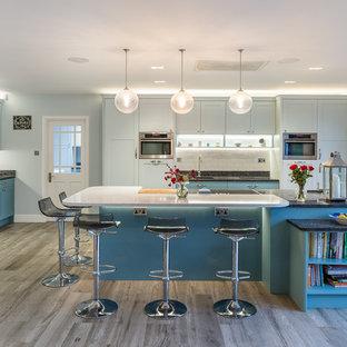 Design ideas for a large classic u-shaped kitchen in Hertfordshire with a built-in sink, shaker cabinets, blue cabinets, granite worktops, white splashback, stone slab splashback, stainless steel appliances, medium hardwood flooring, black worktops, an island and grey floors.