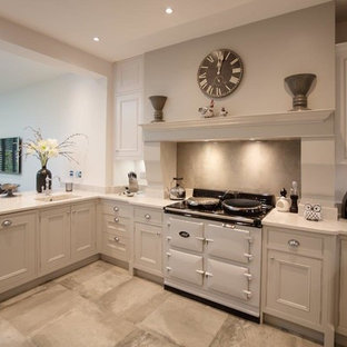 Photo of a mid-sized contemporary u-shaped eat-in kitchen in Hertfordshire with a drop-in sink, shaker cabinets, beige cabinets, granite benchtops, beige splashback, glass sheet splashback, stainless steel appliances, slate floors, no island and beige floor.