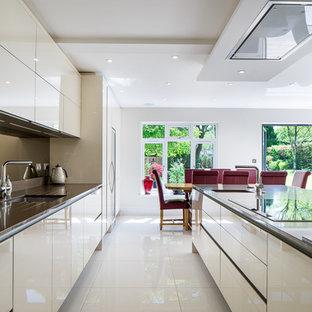 Idéer för ett mycket stort modernt brun kök, med en nedsänkt diskho, släta luckor, vita skåp, bänkskiva i glas, stänkskydd med metallisk yta, spegel som stänkskydd, rostfria vitvaror, skiffergolv, flera köksöar och gult golv