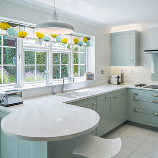 This is an example of a retro l-shaped kitchen in Hertfordshire with a submerged sink, shaker cabinets, blue cabinets, a breakfast bar and white floors.