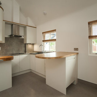 Mid-sized modern u-shaped eat-in kitchen in Hertfordshire with flat-panel cabinets, white cabinets, wood benchtops, a peninsula, a drop-in sink, grey splashback, slate splashback, stainless steel appliances, ceramic floors and grey floor.