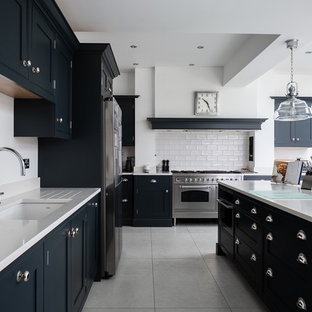 Design ideas for a traditional l-shaped kitchen in Hertfordshire with a submerged sink, beaded cabinets, black cabinets, white splashback, metro tiled splashback, stainless steel appliances, an island, grey floors and white worktops.