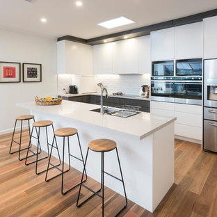 This is an example of a contemporary single-wall eat-in kitchen in Melbourne with an undermount sink, flat-panel cabinets, white cabinets, white splashback, white appliances, medium hardwood floors, with island, brown floor, granite benchtops and subway tile splashback.