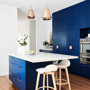 This is an example of a mid-sized contemporary galley eat-in kitchen in Melbourne with an undermount sink, blue cabinets, quartz benchtops, white splashback, engineered quartz splashback, stainless steel appliances, light hardwood floors, with island, brown floor and white benchtop.
