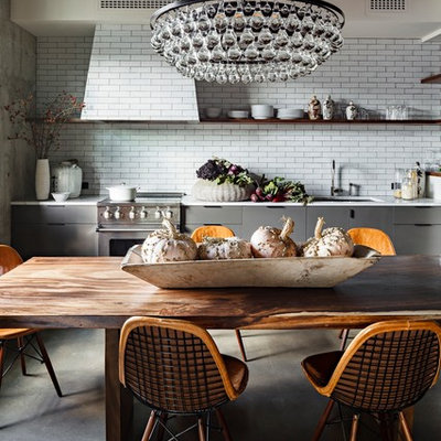 Eat-in kitchen - industrial eat-in kitchen idea in Portland with flat-panel cabinets, gray cabinets, white backsplash, subway tile backsplash, stainless steel appliances and an undermount sink