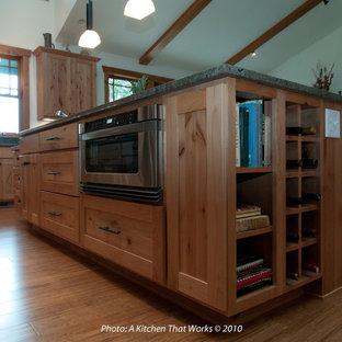 Inspiration för stora amerikanska grönt kök, med en undermonterad diskho, skåp i shakerstil, skåp i mellenmörkt trä, granitbänkskiva, grönt stänkskydd, stänkskydd i sten, rostfria vitvaror, bambugolv, en köksö och beiget golv