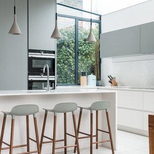 ロンドンの大きいエクレクティックスタイルのおしゃれなキッチン (ドロップインシンク、フラットパネル扉のキャビネット、グレーのキャビネット、白いキッチンパネル、セラミックタイルのキッチンパネル、シルバーの調理設備の、セラミックタイルの床) の写真