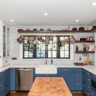 Идея дизайна: п-образная кухня-гостиная среднего размера в стиле шебби-шик с раковиной в стиле кантри, фасадами с утопленной филенкой, синими фасадами, мраморной столешницей, белым фартуком, фартуком из плитки кабанчик, техникой из нержавеющей стали, темным паркетным полом, островом и коричневым полом