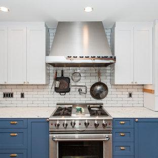 ワシントンD.C.の中サイズのシャビーシック調のおしゃれなキッチン (エプロンフロントシンク、落し込みパネル扉のキャビネット、青いキャビネット、大理石カウンター、白いキッチンパネル、サブウェイタイルのキッチンパネル、シルバーの調理設備の、濃色無垢フローリング) の写真