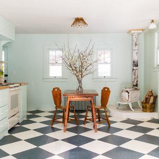ニューヨークのシャビーシック調のおしゃれなキッチン (フラットパネル扉のキャビネット、ターコイズのキャビネット、木材カウンター、白いキッチンパネル、サブウェイタイルのキッチンパネル、塗装フローリング、アイランドなし、マルチカラーの床、茶色いキッチンカウンター) の写真