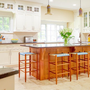 This is an example of a large country kitchen in Charlotte with an undermount sink, shaker cabinets, white cabinets, granite benchtops, white splashback, ceramic splashback, stainless steel appliances, porcelain floors, with island, beige floor and black benchtop.