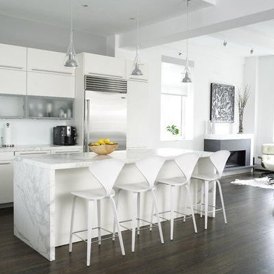 Example of a trendy open concept kitchen design in New York with white cabinets, marble countertops, stainless steel appliances, gray countertops and flat-panel cabinets