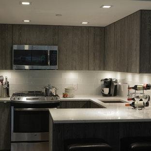 Imagen de cocina en U, actual, de tamaño medio, cerrada, con fregadero bajoencimera, armarios con paneles lisos, puertas de armario grises, encimera de terrazo, salpicadero blanco, salpicadero de azulejos de vidrio, electrodomésticos de acero inoxidable y península