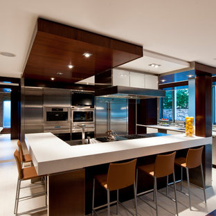 Trendy white floor open concept kitchen photo in New York with flat-panel cabinets, white cabinets, multicolored backsplash, matchstick tile backsplash, stainless steel appliances, an island and white countertops