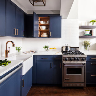 Small contemporary kitchen remodeling - Small trendy u-shaped dark wood floor and brown floor kitchen photo in New York with a farmhouse sink, blue cabinets, white backsplash, stainless steel appliances, white countertops, flat-panel cabinets, quartzite countertops, subway tile backsplash and no island