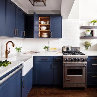 Kleine Moderne Küche ohne Insel in U-Form mit Landhausspüle, blauen Schränken, Küchenrückwand in Weiß, Küchengeräten aus Edelstahl, dunklem Holzboden, braunem Boden, weißer Arbeitsplatte, flächenbündigen Schrankfronten, Quarzit-Arbeitsplatte und Rückwand aus Metrofliesen in New York