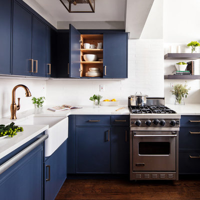 Small trendy dark wood floor and brown floor kitchen photo in New York with a farmhouse sink, blue cabinets, white backsplash, stainless steel appliances, white countertops, flat-panel cabinets, quartzite countertops, subway tile backsplash and no island