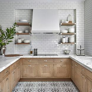 На фото: кухня в стиле современная классика с врезной раковиной, фасадами с утопленной филенкой, светлыми деревянными фасадами, столешницей из кварцита, белым фартуком, фартуком из керамической плитки, полом из керамогранита, полуостровом, разноцветным полом и белой столешницей