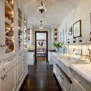 Traditional kitchen pantry designs - Example of a classic galley brown floor and dark wood floor kitchen pantry design in Chicago with recessed-panel cabinets, white cabinets, marble countertops, white backsplash, marble backsplash, an island, white countertops and a farmhouse sink