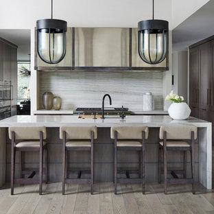 Foto di una cucina abitabile design con ante lisce, ante marroni, top in quarzite, paraspruzzi grigio, paraspruzzi in lastra di pietra, elettrodomestici colorati, parquet chiaro, isola, pavimento grigio e top grigio