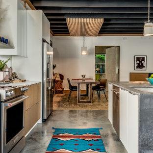 Стильный дизайн: параллельная кухня среднего размера в стиле фьюжн с обеденным столом, врезной раковиной, плоскими фасадами, светлыми деревянными фасадами, столешницей из бетона, розовым фартуком, фартуком из терракотовой плитки, техникой из нержавеющей стали, бетонным полом, островом, серым полом, балками на потолке и серой столешницей - последний тренд
