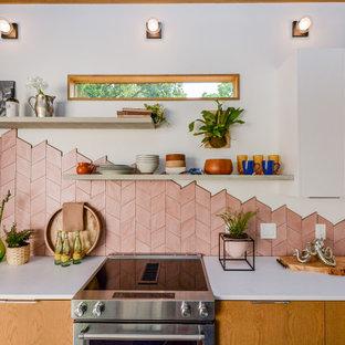 ヒューストンの中くらいのエクレクティックスタイルのおしゃれなキッチン (アンダーカウンターシンク、フラットパネル扉のキャビネット、淡色木目調キャビネット、コンクリートカウンター、ピンクのキッチンパネル、テラコッタタイルのキッチンパネル、シルバーの調理設備、コンクリートの床、グレーの床、白いキッチンカウンター、表し梁) の写真