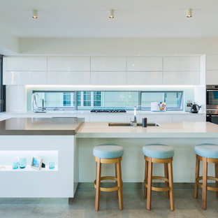 Photo of an expansive contemporary kitchen in Cairns with white cabinets, solid surface benchtops, stainless steel appliances, porcelain floors, with island, grey floor, white benchtop, an undermount sink, flat-panel cabinets and window splashback.
