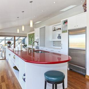 Idéer för att renovera ett avskilt, mellanstort funkis röd linjärt rött kök, med en undermonterad diskho, släta luckor, vita skåp, rostfria vitvaror, mörkt trägolv, en köksö, bänkskiva i kvarts och brunt golv