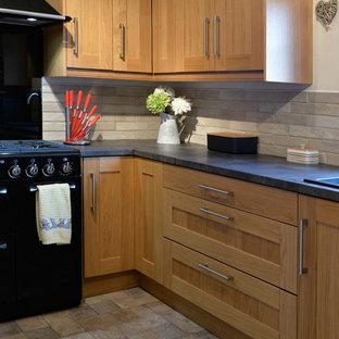 Esempio di una cucina a L minimalista chiusa e di medie dimensioni con lavello da incasso, ante in stile shaker, ante marroni, top in laminato, paraspruzzi nero, paraspruzzi con lastra di vetro, elettrodomestici neri, pavimento in laminato, nessuna isola, pavimento beige e top nero