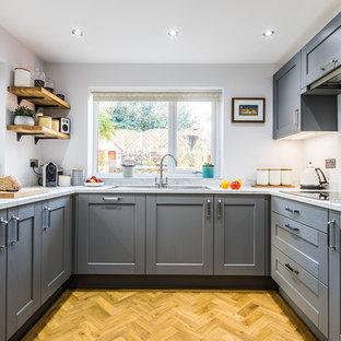 他の地域の中サイズのトランジショナルスタイルのおしゃれなキッチン (シェーカースタイル扉のキャビネット、グレーのキャビネット、ラミネートカウンター、白いキッチンパネル、ガラス板のキッチンパネル、パネルと同色の調理設備、クッションフロア、茶色い床、白いキッチンカウンター、ドロップインシンク) の写真