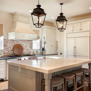 Klassisk inredning av ett stort kök, med en rustik diskho, skåp i shakerstil, vita skåp, integrerade vitvaror, mörkt trägolv, en köksö, bänkskiva i täljsten och stänkskydd i tegel