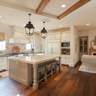 Huge elegant u-shaped dark wood floor and brown floor open concept kitchen photo in Houston with a farmhouse sink, recessed-panel cabinets, distressed cabinets, brick backsplash, stainless steel appliances and an island