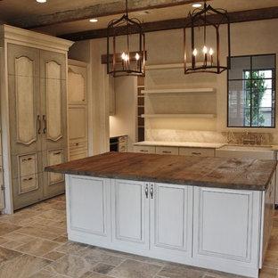 Modelo de cocina comedor en U, rural, grande, con fregadero sobremueble, puertas de armario blancas, encimera de madera, salpicadero beige, salpicadero de losas de piedra, electrodomésticos con paneles, suelo de mármol y una isla