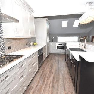 シカゴの大きいエクレクティックスタイルのおしゃれなキッチン (エプロンフロントシンク、シェーカースタイル扉のキャビネット、オレンジのキャビネット、クオーツストーンカウンター、グレーのキッチンパネル、ガラスタイルのキッチンパネル、シルバーの調理設備の、クッションフロア、茶色い床、グレーのキッチンカウンター) の写真