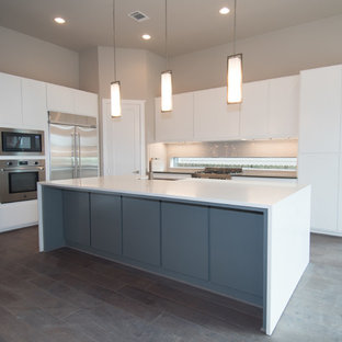 Large contemporary open concept kitchen photos - Large trendy l-shaped dark wood floor and brown floor open concept kitchen photo in Houston with an undermount sink, flat-panel cabinets, white cabinets, solid surface countertops, white backsplash, glass sheet backsplash, stainless steel appliances and an island