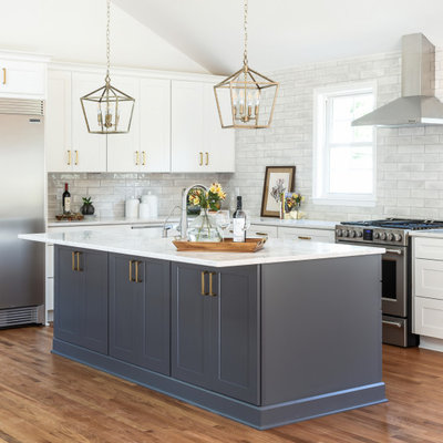 Inspiration for a large transitional l-shaped brown floor and medium tone wood floor kitchen remodel in Nashville with shaker cabinets, white cabinets, quartz countertops, gray backsplash, subway tile backsplash, stainless steel appliances, an island and white countertops